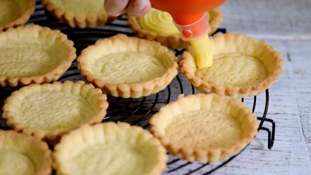 girl fills tartlets with custard. pastry. sweet tartlets dessert. - nadziewany placek filmów i materiałów b-roll