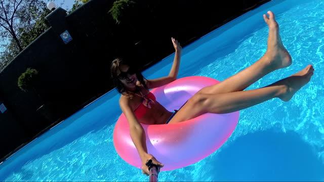 flicka flyter på en uppblåsbar cirkel i poolen - inflatable ring bildbanksvideor och videomaterial från bakom kulisserna