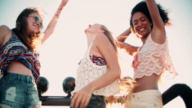 Girl friends dancing in vehicle at beach on road trip video