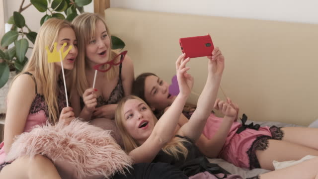 Girl friends taking selfie while posing with fake props on bed Teenage girls having fun taking selfie while posing with fake props during pajama party at home prop stock videos & royalty-free footage
