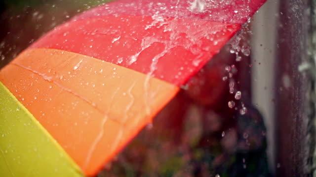 mädchen versteckt unter sonnenschirmen aus regen - sonnenschirm stock-videos und b-roll-filmmaterial