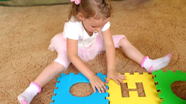 Girl gather large soft puzzle sitting on floor. video