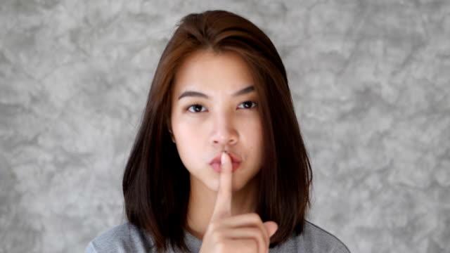 vídeos y material grabado en eventos de stock de chica gesto silencio muestra - dedo sobre labios