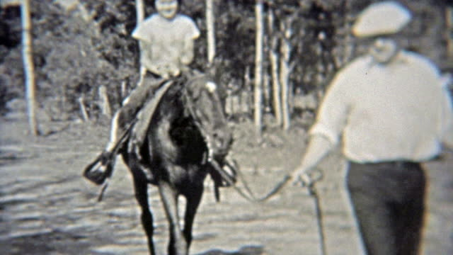 1937: Girl getting horse riding lessons through the forest. video