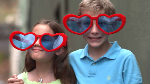 a girl gives a boy a kiss while both are wearing heart shaped sunglasses - kiss стоковые видео и кадры b-roll