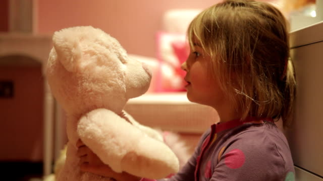 Girl Giving Teddy Bear Hug Whilst Wearing Pajamas Girl talks to teddy bear before giving him big hug.Shot on Canon 5d Mk2 with a frame rate of 30fps stuffed stock videos & royalty-free footage