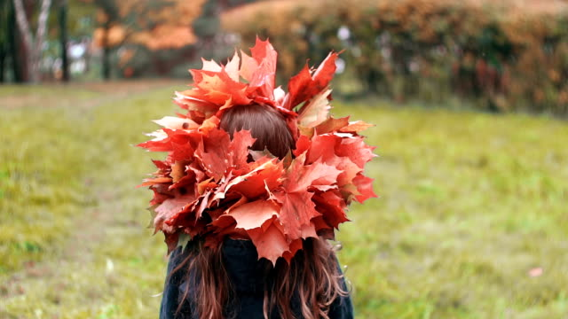 vídeos de stock e filmes b-roll de girl goes back and then turns around and looks at the camera. cute little girl in a wreath crown of autumn maple leaves - coroa
