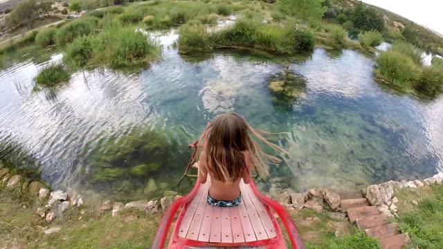 girl going down slide into river - slitta video stock e b–roll