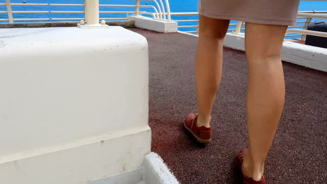 Girl going upstairs to deck, sea trip on cruise liner, endless water horizon