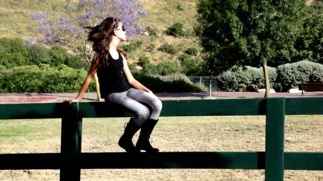 girl greets someone sitting on the fence - endast en tonårsflicka bildbanksvideor och videomaterial från bakom kulisserna