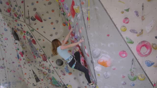 stockvideo's en b-roll-footage met close up: meisje grijpt op een snufje te houden, terwijl ze lussen haar touw in karabijn. - lood