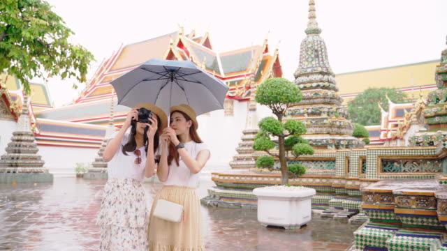 """Girl Guides of Thailand's fellow Japanese to visit the main attractions of the country."""" Wat Pho """" landmark of Bangkok in Thailand.Two Asian women spread umbrellas to explore Thailand's major temples on rainy days"""