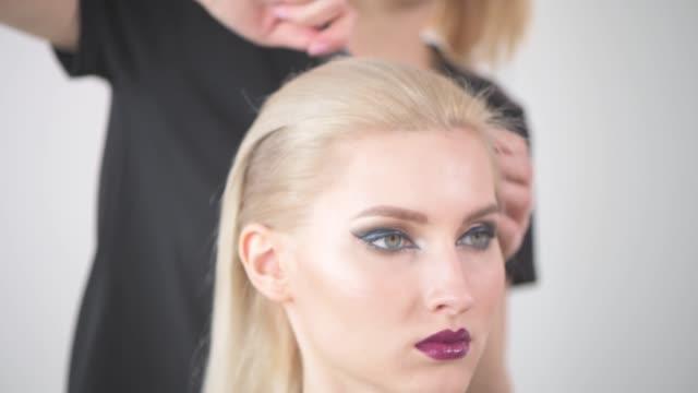 a girl hairdresser does a haircut to a blonde girl. - длина стоковые видео и кадры b-roll
