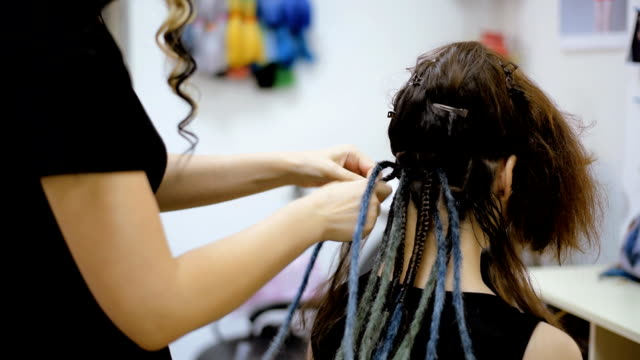 girl hairdresser weaves dreadlocks client in the salon hairdresser braids dreadlocks girl in the salon locs hairstyle stock videos & royalty-free footage