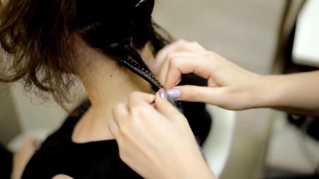 flicka frisör väver dreadlocks klient i salongen - väva bildbanksvideor och videomaterial från bakom kulisserna