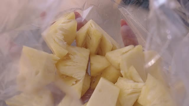 girl hand holds plastic bag with pineapple slices closeup