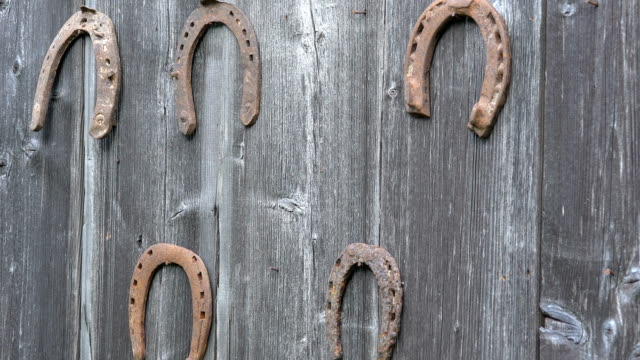 girl hand put retro rusty horseshoes on old wooden rural house wall. closeup. 4k - horseshoe stock videos & royalty-free footage