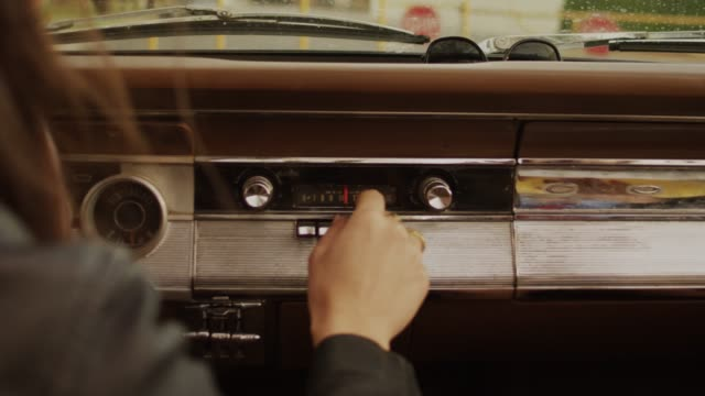 Girl hand tuning radio in a Vintage Classic Car