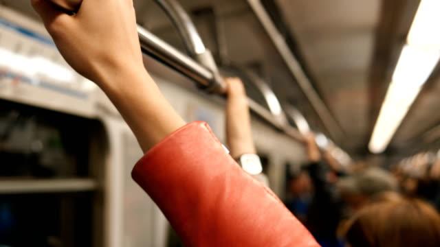 girl hand wearing orange leather jacket holds metro handrail - vídeo
