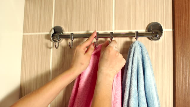 Girl hanging a towel in the bathroom on the hook. video