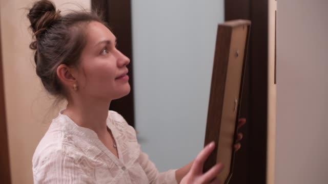 flicka hänger en fotoram på väggen - hänga bildbanksvideor och videomaterial från bakom kulisserna
