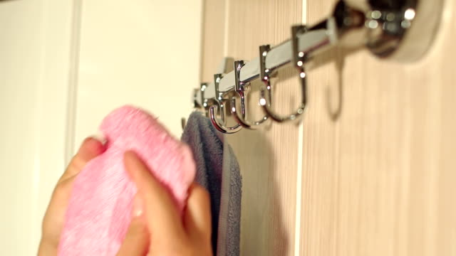 Girl hangs a towel on the hook of hanger,close-up. video