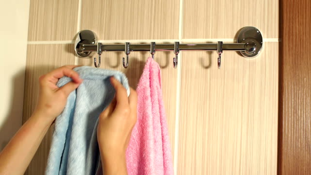 Girl hangs a towel on the hook of the hanger. video