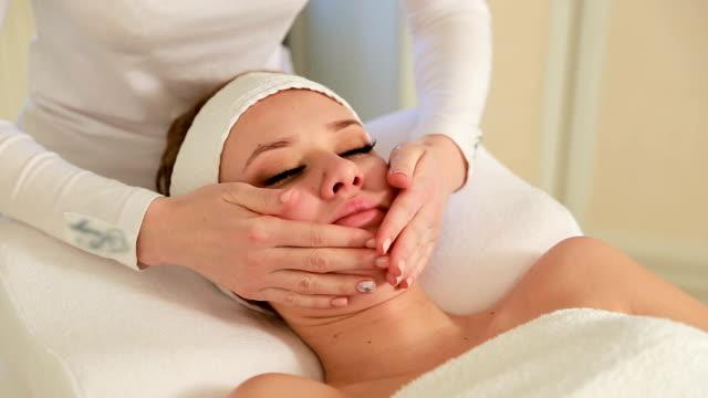 Girl having facial massage Girl having facial massage. Doctor cosmetologist doing facial massage for girl beautician stock videos & royalty-free footage