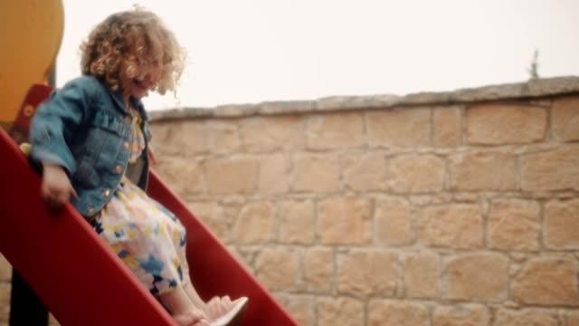 stockvideo's en b-roll-footage met meisje van plezier op kleuterschool speeltuin dia tijdens reces van de school - blond curly hair