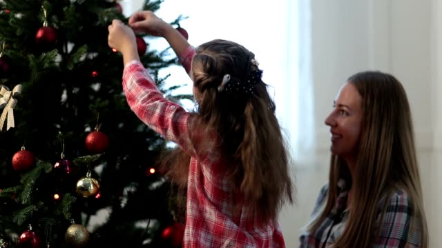 Girl helping her mom to decorate family xmas tree video