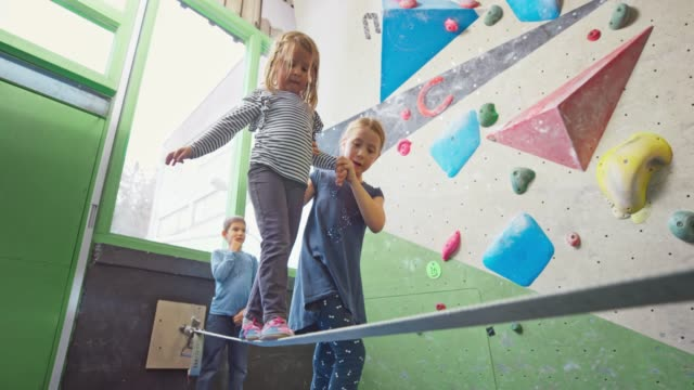 girl helping her younger sister walk on the slackline in the gym - balance video stock e b–roll