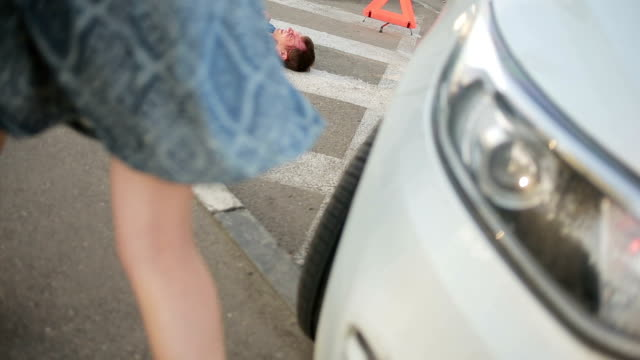 Girl helping injured in a car accident man. pedestrian injured in road accidents video