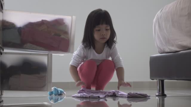 vídeos de stock, filmes e b-roll de garota ajudar com família afazeres domésticos. dobrar suas roupas e mantém na cômoda. - afazeres domésticos