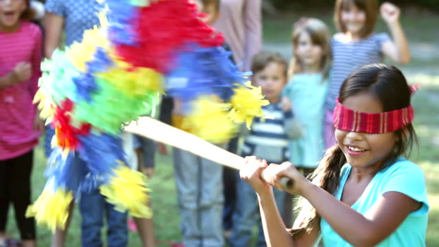Girl hitting pinata, children watching in background video
