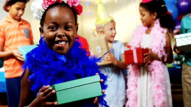 Girl holding a gift box during birthday party at home 4k video