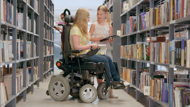 DS Girl holding a tablet handing a book to a woman in the wheelchair Medium dolly shot of a blonde girl holding a tablet in her hands taking a book off the shelf in library and handing it to young woman in wheelchair. disability stock videos & royalty-free footage