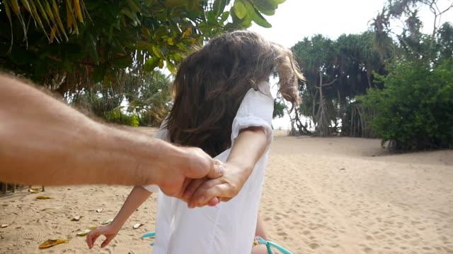 Meisje mannenhand houden en draait op tropische exotische strand naar de Oceaan. Volg mij schot voor pull-jonge vrouw haar vriendje op de kust. Zomervakantie of vakantie. Oogpunt. POV Slow motion video