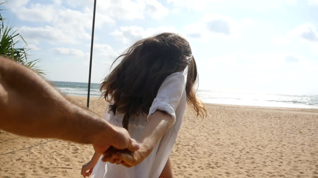 Girl holding male hand and running on tropical exotic beach to the ocean. Follow me shot of young woman pull her boyfriend on the sea shore. Summer vacation or holiday. Point of view. POV Slow motion video