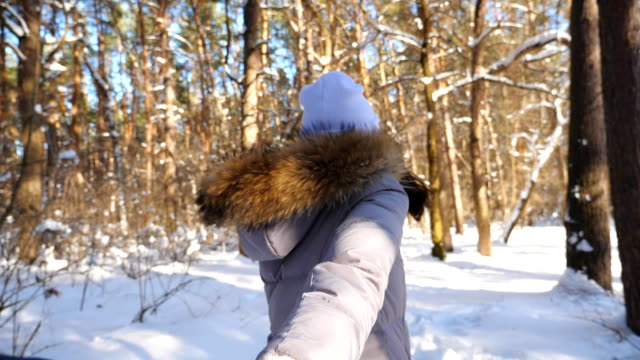 Girl holding male hand and running through snowy forest at cold sunny day. Follow me shot of young woman pulling her boyfriend in winter wood. Scenic winter environment. POV Slow motion Close up