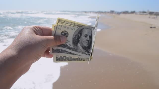 girl holding money bill of 300 dollars on background of sea waves - badawczy statek kosmiczny filmów i materiałów b-roll