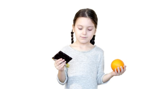 Girl holding orange and chocolate. She has to choose one.