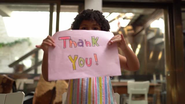 stockvideo's en b-roll-footage met de holdingsdocument van het meisje met 'dank u' die thuis wordt geschreven - webcampunt van mening - bord bericht