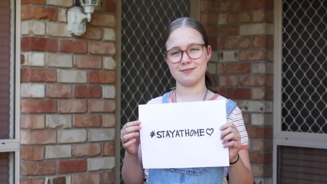 vídeos y material grabado en eventos de stock de girl holding stay at home sign - stay home