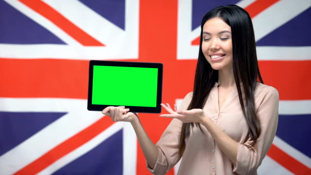Girl holding tablet with green screen, British flag on background, migration