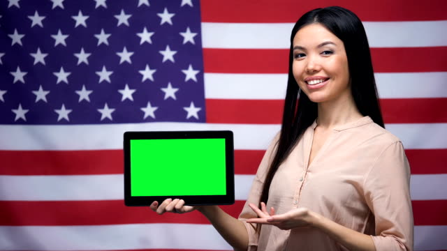 Girl holding tablet with green screen, USA flag on background, migration
