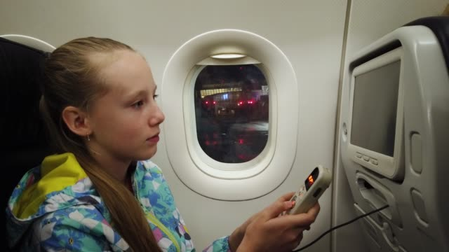Girl holding the remote controller for entertainment system in the airplane