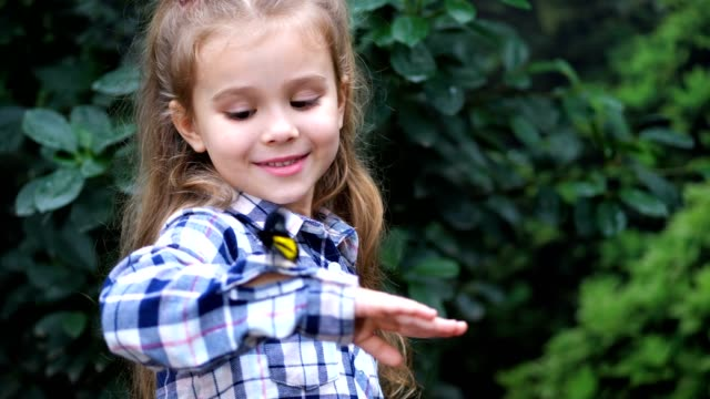 A girl holds a butterfly on her hand, smiles. The butterfly flies away, the girl looks surprised. 4K Slow Mo A girl holds a butterfly on her hand, smiles. The butterfly flies away, the girl looks surprised. butterfly insect stock videos & royalty-free footage