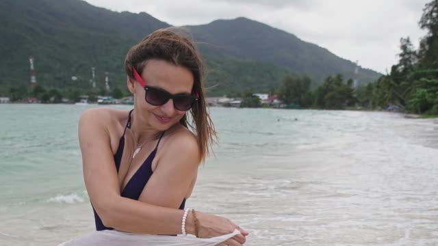flickan håller i händerna en pareo på en tropisk strand. - sarong bildbanksvideor och videomaterial från bakom kulisserna
