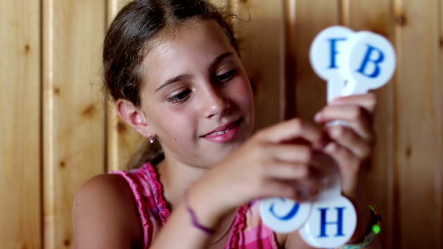 Girl holds in hands English alphabet - video