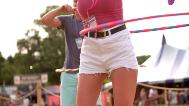 Girl hula-hooping at a music festival, slow motion video